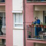 Twee mensen op hun eigen balkon. Ze klappen en kijken om zich heen.