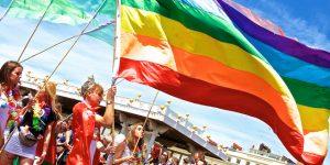 Homo: Foto van bezoekers van de Brighton Pride met een regenboogvlag.