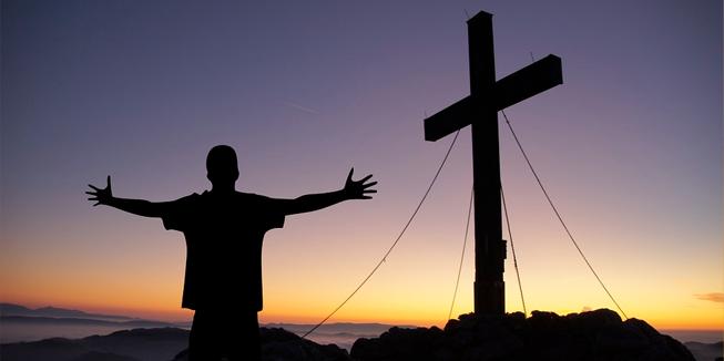 Een jongen met zijn armen gespreid, bij een kruis.