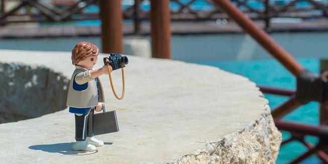 Een Playmobil-poppetje maakt een foto tijdens een dagje uit.