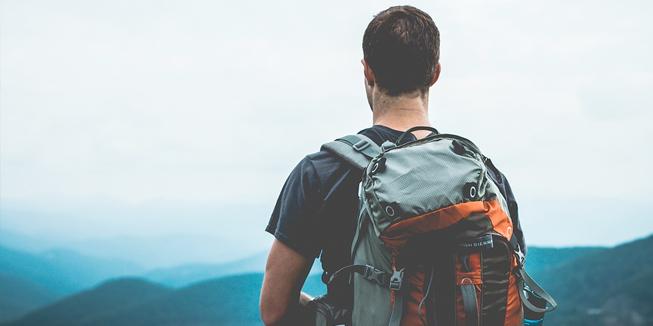 Een reiziger met rugzak kijkt uit over een landschap in Europa